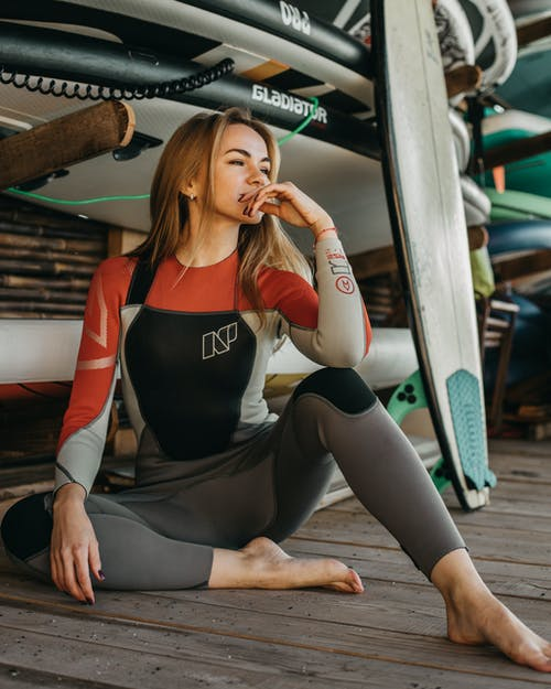 Woman in Black Tank Top and Black Leggings Sitting on Wooden Bench