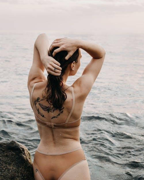 Woman in Brown Bikini Standing on Brown Rock Near Body of Water