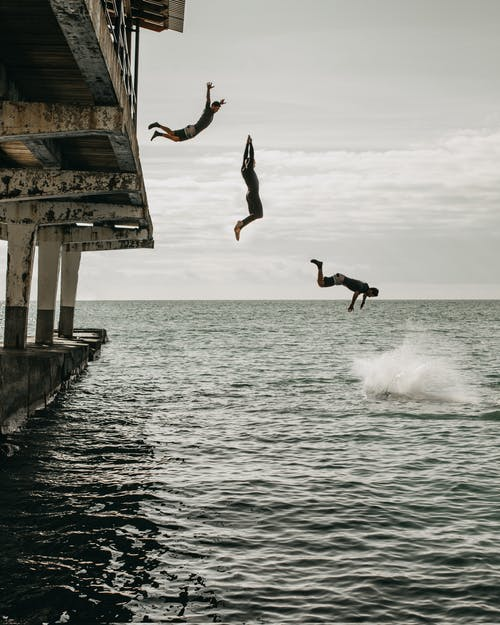 Man in Black Shirt and Pants Jumping on Sea Dock