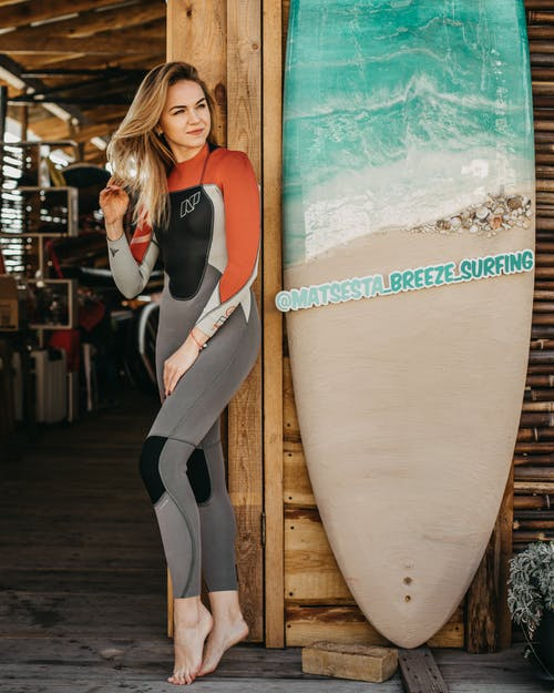 Full length of positive young female with blond hair in wetsuit standing near wooden wall of house with surfing boards and looking away in daytime