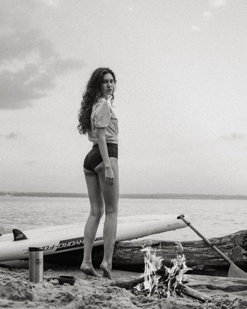 Woman in Black Bikini Standing on White Surfboard on Beach