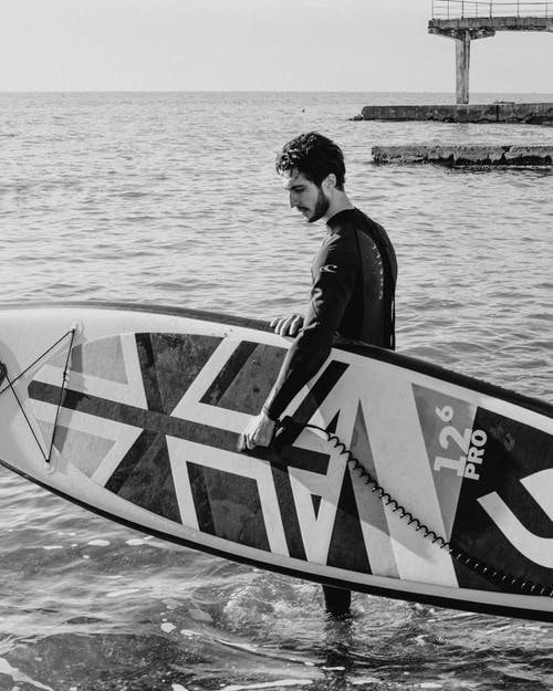 Man in Black Jacket and Pants Riding on White and Black Surfboard