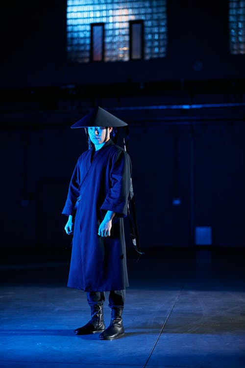 Woman in Blue Academic Dress Standing on Gray Concrete Floor
