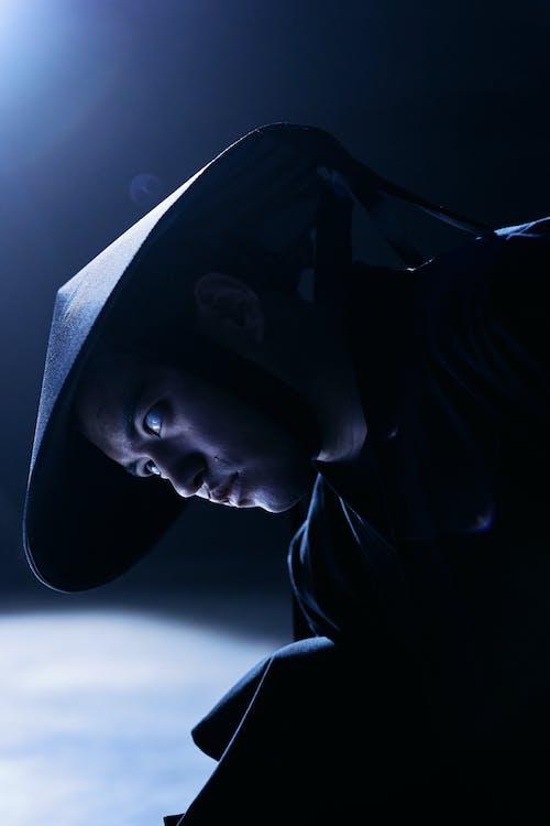 Man in Black Hoodie Wearing Black Hat