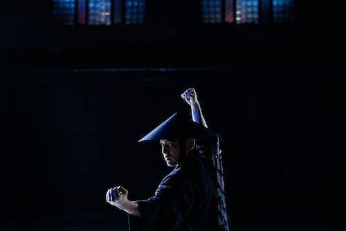 Man in Black Shirt Wearing Black Hat