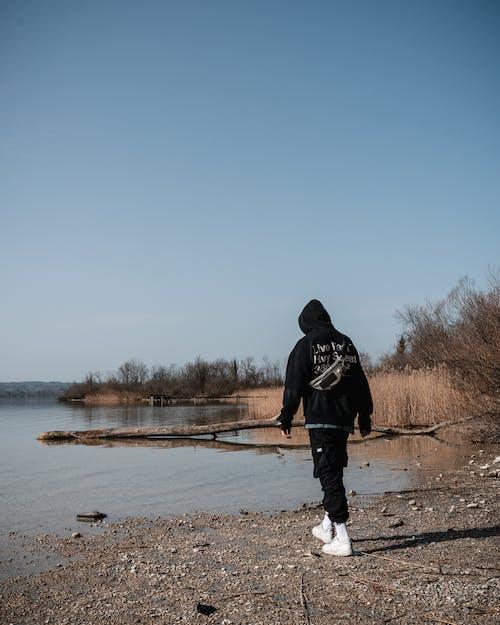 Man in Black Hoodie Standing on Brown Field Near Body of Water