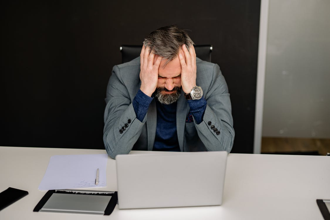Man in Gray Suit Jacket Covering His Face With His Hand, stressed before delegating tasks