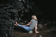 Woman in Black and White Striped Shirt and Blue Denim Jeans Sitting on Ground