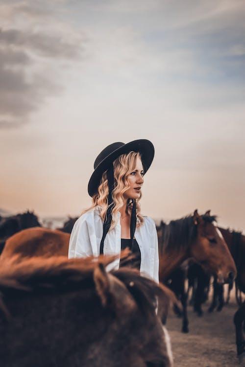 Woman in Blue Denim Jacket and Black Hat Standing Beside Brown Horse