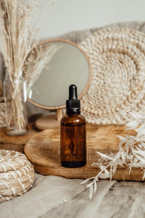 Kostenloses Stock Foto zu glasflaschen, holztablett, kosmetik-produkt
