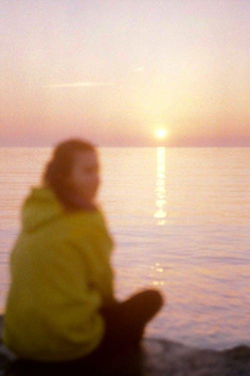 Girl in Yellow Hoodie Sitting on Beach