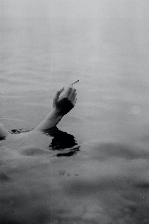 Black and white of crop unrecognizable person smoking cigarette while swimming in sea water