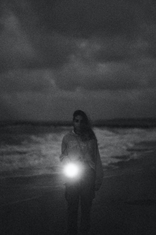 Woman with lamp standing on seashore