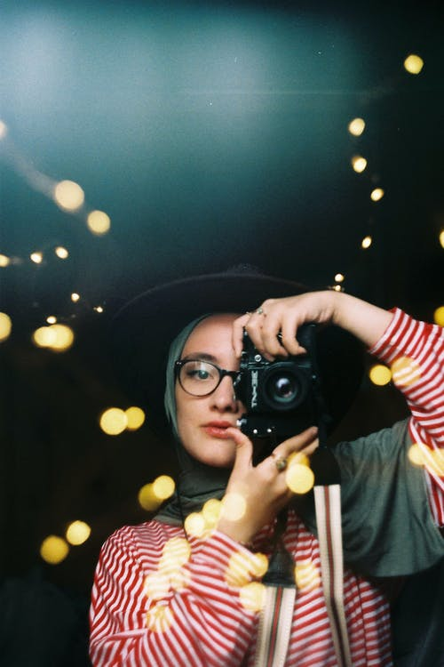 Stylish female with dyed hair in hat taking picture on photo camera among blurred lights of garland