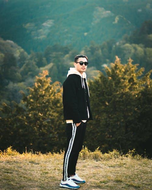 Man in Black Coat Standing on Green Grass Field
