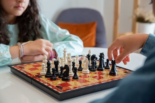 Person Playing Chess on Chess Board