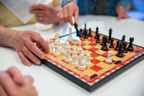 Person Playing Chess With Chess Pieces