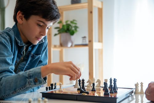 Woman in Blue Denim Jacket Holding Brown Wooden Chess Board