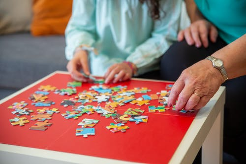 People Playing Jigsaw Puzzle