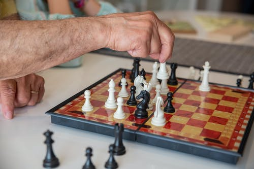 Person Holding Chess Piece on Chess Board