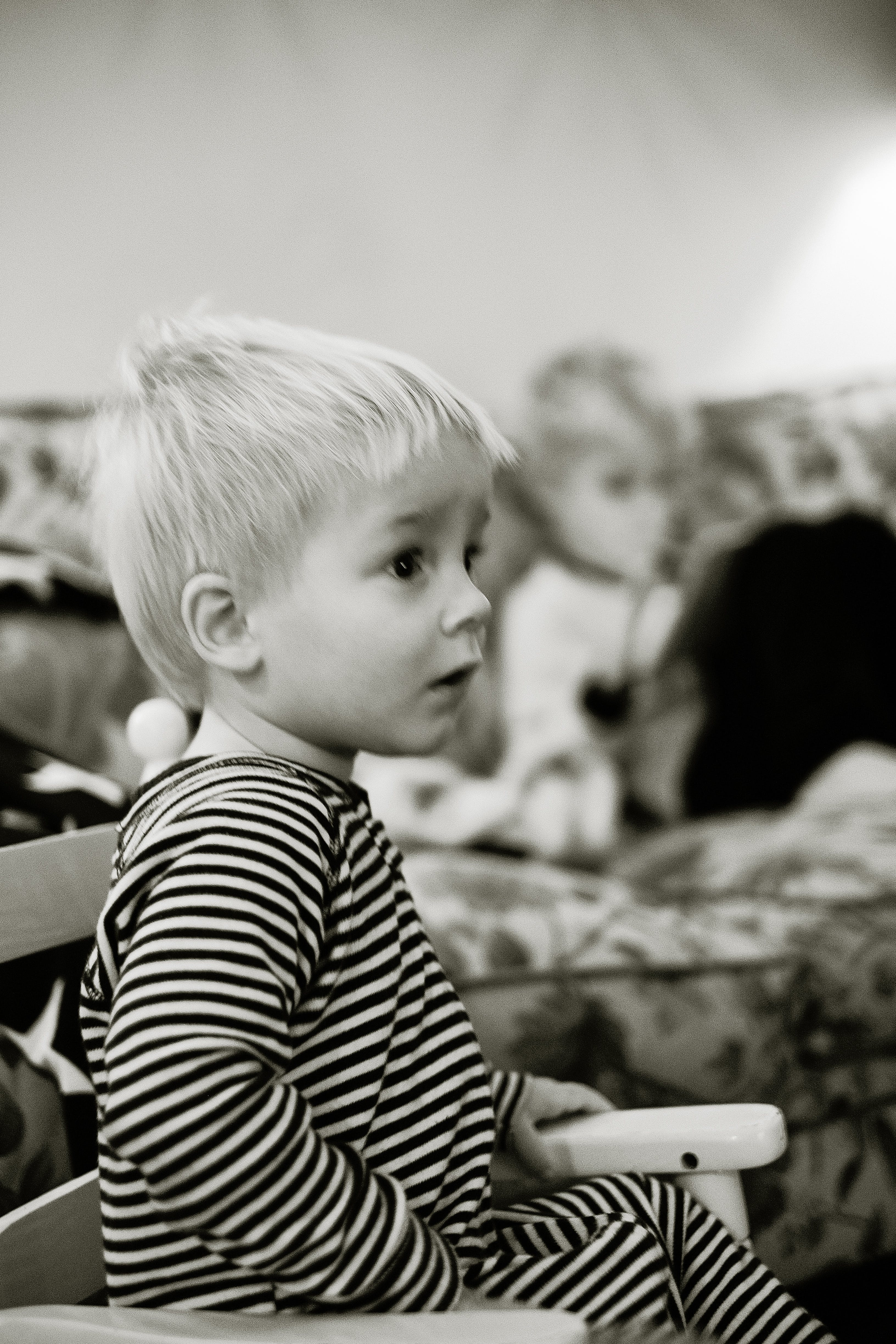 Grayscale Photo of Boy Sitting on Armchair