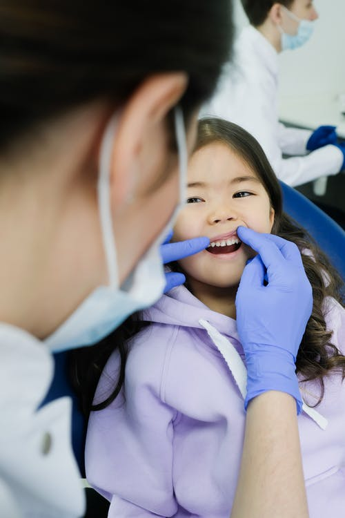 Child Having a Check up to a Dentist
