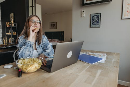 Woman Eating and Using a Laptop