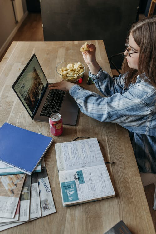 Woman Sitting at the Table and Using Laptop