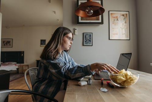 Woman Using a Laptop While Eating
