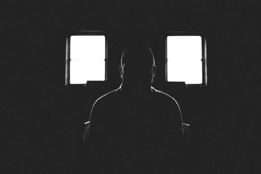 Person Sitting in Dark Room With 2 Window