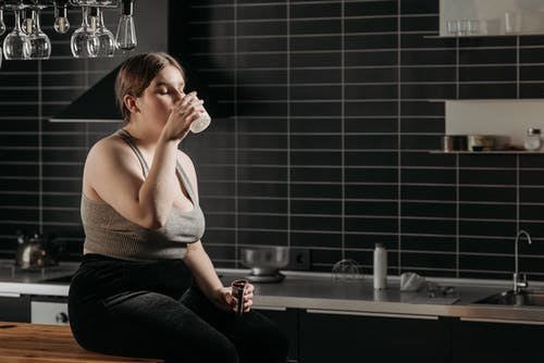 Woman Sitting on Table and Drinking Milk