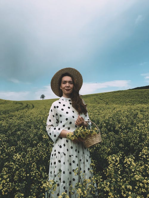 Charming woman with flowers in field