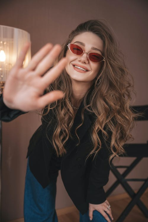 Happy woman in stylish wear showing hand to camera