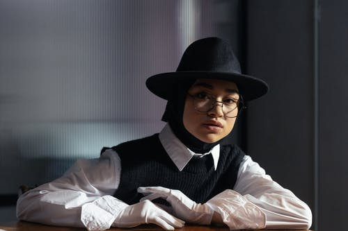 Woman in White Long Sleeve Shirt Wearing Black Hat