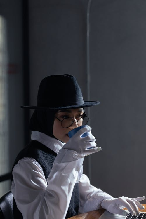 Won Wearing a Black Hat and Black Vest Drinking