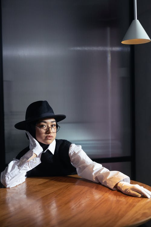 Man in White Dress Shirt and Black Hat Leaning on a Table