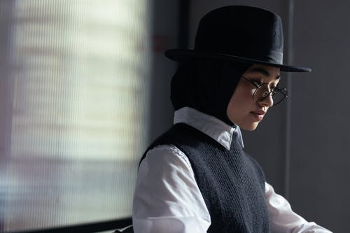 Woman in White Dress Shirt and Black Vest Wearing Black Fedora Hat