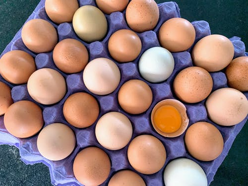 Brown and White Eggs on Blue Plastic Container