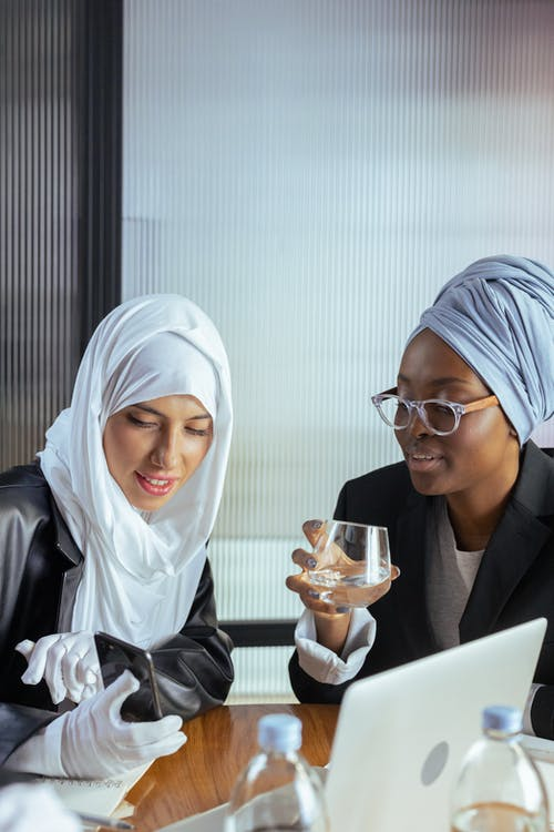Woman in White Hijab Holding a Smartphone