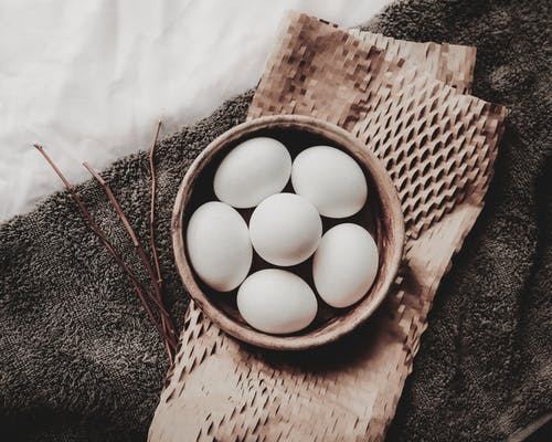 Raw eggs in wicker bowl placed above paper