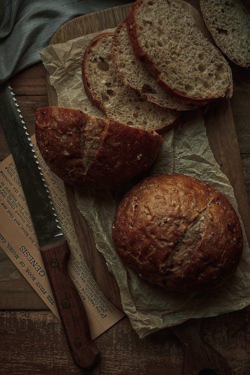 A Bread Knife beside Breads on a Wooden Chopping Board