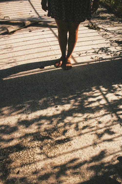 Person Walking on Gray Concrete Road