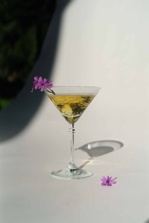 Crystal glass with alcoholic sparkling drink and delicate purple flowers placed on white background