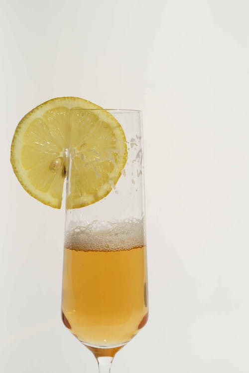 Glass of refreshing alcohol beverage with foam served with slice of sour lemon on white background