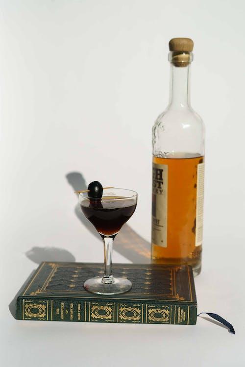 Manhattan cocktail with bottle of brandy