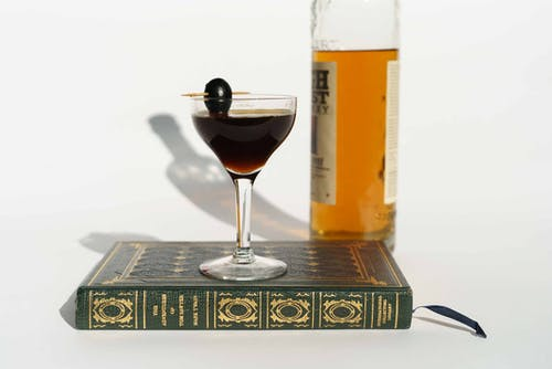 Martini cocktail on book near bottle of whiskey