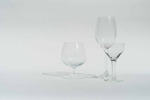 Various transparent empty crystal glasses prepared for alcohol beverages against white background in studio
