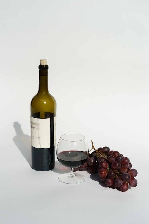 Red Wine Bottle beside a Wine Glass