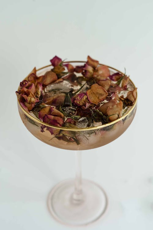 High angle of glass filled with cold refreshing drink and dried herbs and ice on white background