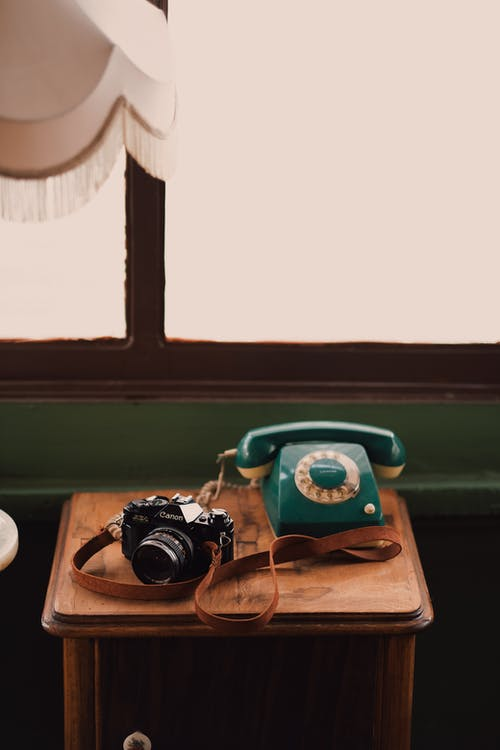 Retro photo camera and vintage telephone placed on wooden bedside table